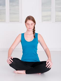 woman sitting cross legged with eyes closed