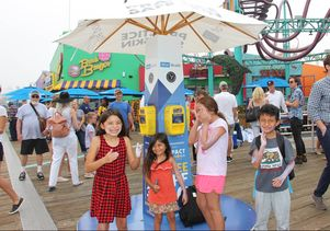 Children slather on free SPF 30 sunscreen from a new sun-safety station on the Santa Monica Pier.