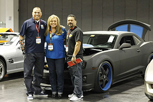 From left, Marine Staff Sgt. Octavio Sanchez, Stephany Wigington and Herb Grageda of LINE-X and the customized Camaro that was auctioned off.